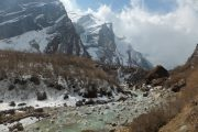 Walking through the valley, along the river, snowy mountains on the way to Annapurna Base Camp