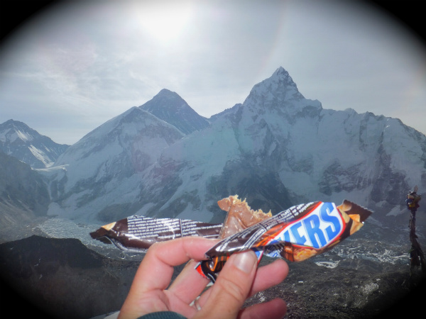 Nepal Trekking Information: Eating a Snickers bar on Kala Patthar Looking at Everest