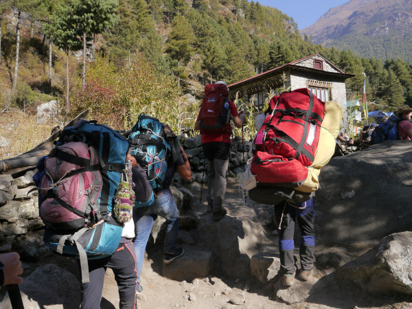 Porters carrying very heavy loads